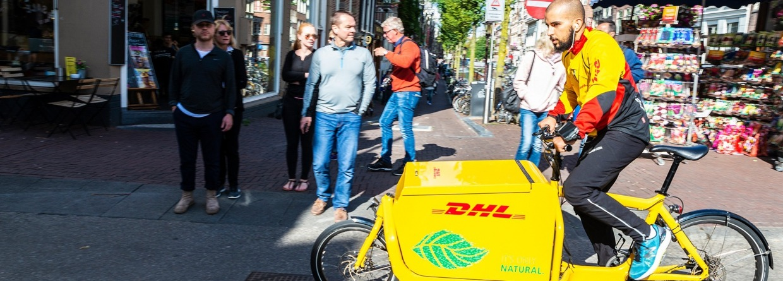 Jonge mens op leveringsfiets die in Amsterdam, Nederland circuleert, schade zakelijk, e-bike, verzekeringen, zakelijke e-bike
